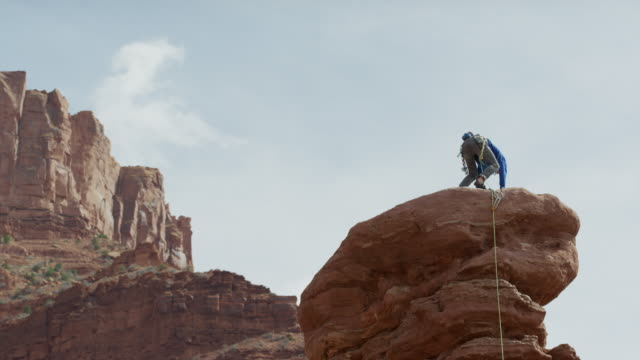 vídeos de stock e filmes b-roll de wide low angle panning shot of man standing on rock formation / fisher towers, utah, united states - equipamento de alpinismo