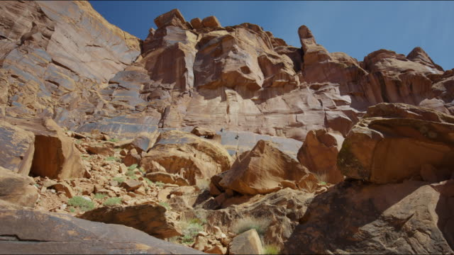 wide low angle panning shot of rocks in desert landscape / moab, utah, united states - wide stock-videos und b-roll-filmmaterial
