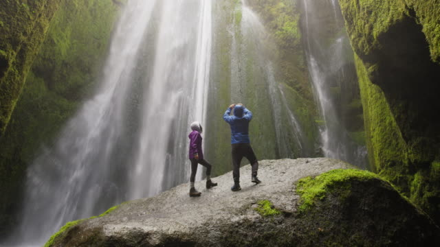 wide low angle shot of couple standing on rock photographing waterfall / rangarvallasysla, iceland - young couple stock videos & royalty-free footage