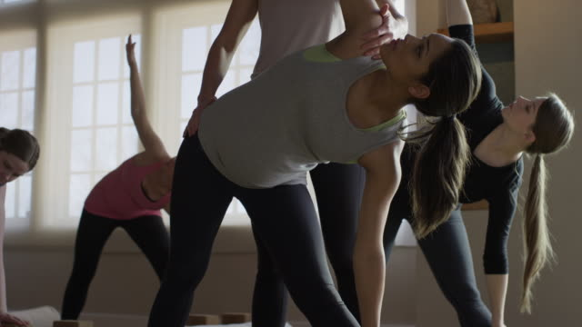 Wide low angle shot of expectant mothers and instructor in yoga class / Provo, Utah, United States