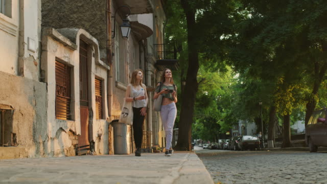 vídeos y material grabado en eventos de stock de wide low angle shot of women sightseeing on sidewalk / plovdiv, bulgaria - sin mangas