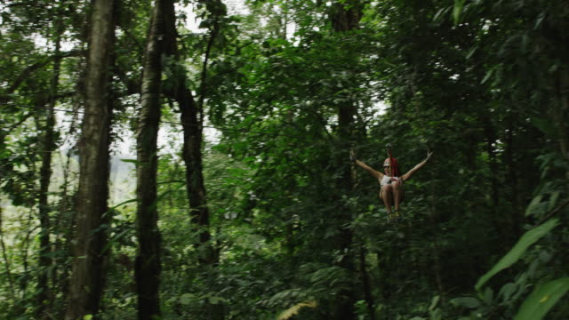 wide low angle tracking shot of woman ziplining in rain forest / quepos, puntarenas, costa rica - ロープスライダー点の映像素材/bロール