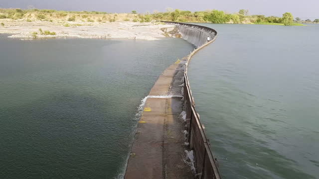 wide, man crossing the parichha dam on the betwa river in india - dam stock videos & royalty-free footage