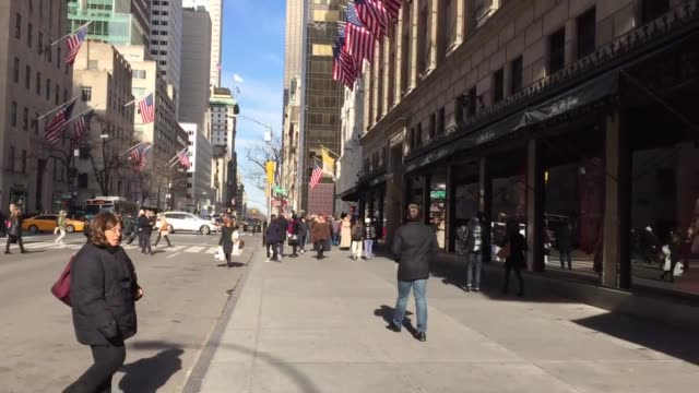 Wide medium close and pans of flagship store customers and saks shopping bag