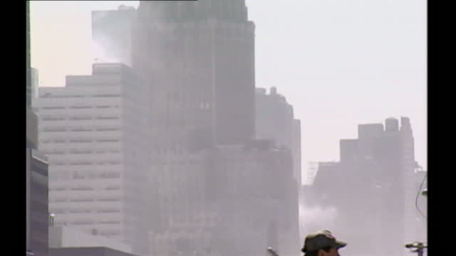 wide, minimal panning of the new york skyline, high rise building and dusty air around the ground zero site. a lone man with his hands on his hips... - september 11 2001 attacks stock videos & royalty-free footage