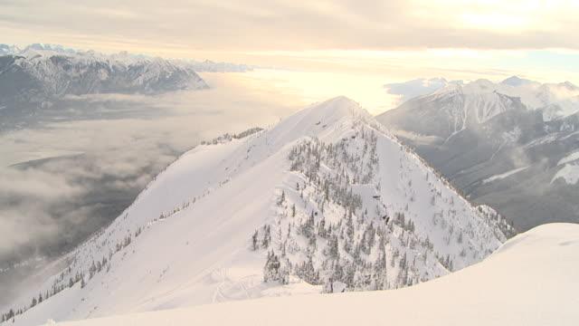 vídeos de stock e filmes b-roll de pan wide mountain ranges from peak / golden, british columbia, canada - snowboard