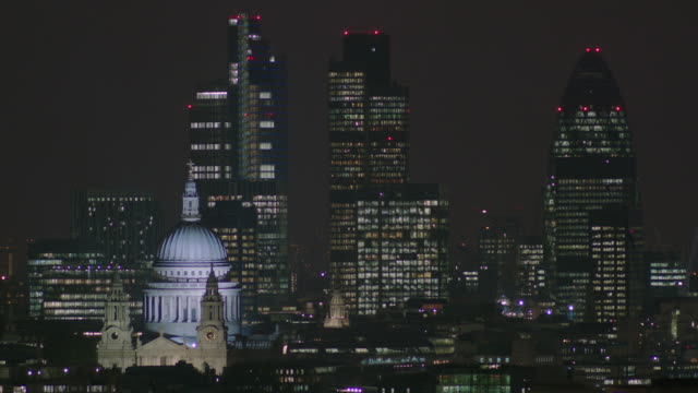 Wide, nighttime shot of City of London buildings including St Paul's Cathedral and the 'Gherkin', London, UK.