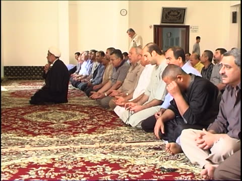 wide of a shia sheikh and worshippers facing the mihrab kneeling during prayer in a mosque. - 信者点の映像素材/bロール