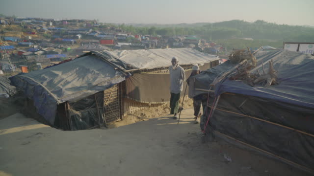 Wide of camp when two old men walk out from behind a home in Kutupalong refugee camp in Bangladesh Fleeing persecution by the Myanmar government and...