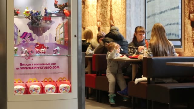 wide of mcdonalds cafe in moscow russia on tuesday 28th october diners sit beside a case advertising happy meals young diners play an interactive... - happy meal stock videos & royalty-free footage