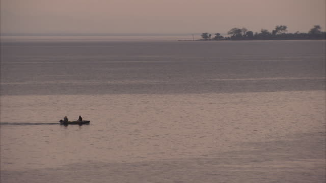 Wide of shot of small boat travelling across rainy river at dusk