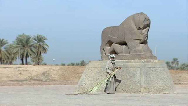 wide on a man sweeping the ground with a palm frond around the statue of the lion of babylon. since the gulf war occupying forces have caused... - frond stock videos & royalty-free footage