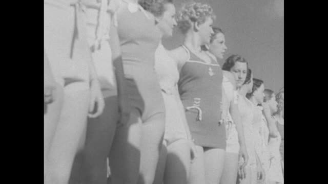 vidéos et rushes de wide overhead shot of contestants in bathing suits parading along walkways in middle of pool / line of contestants walking out to pool / close shot... - concurrent