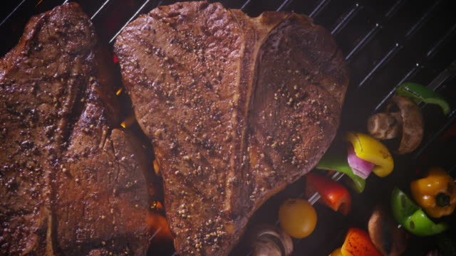 wide overhead two t-bone steaks on a grill - zoom in to extreme close up of the meat. - メタルグリッド点の映像素材/bロール