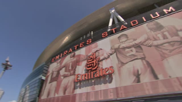 vídeos de stock e filmes b-roll de wide pan from l to r showing one side of the emirates stadium with dennis bergkamp, bob wilson, eddie hapgood, charlie george immortalised in the... - bob wilson futebol