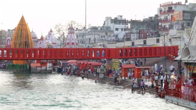 a wide pan of the bathing ghats on ganges' banks wth pilgrims at har ki pauri in haridwar, india - wide stock videos and b-roll footage