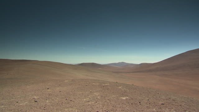 wide pan over brown, dusty hills and an intense blue sky in the atacama desert, chile. - atacama region stock videos & royalty-free footage