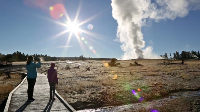wide pan shot of two young girls standing on boardwalk backlight and taking photo by rising sun while old faithful erupts in water and steam. - old faithful stock videos & royalty-free footage