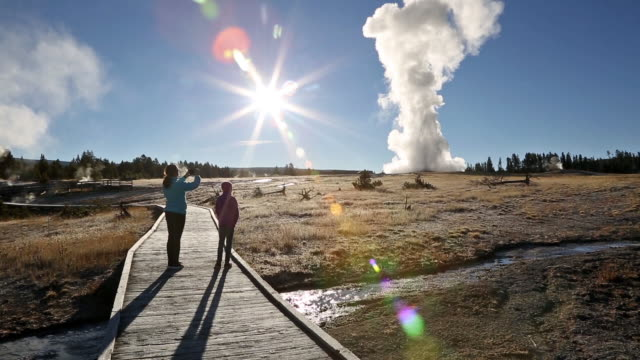 vidéos et rushes de wide pan shot of two young girls standing on boardwalk backlight and taking photo by rising sun while old faithful erupts in water and steam. - geyser
