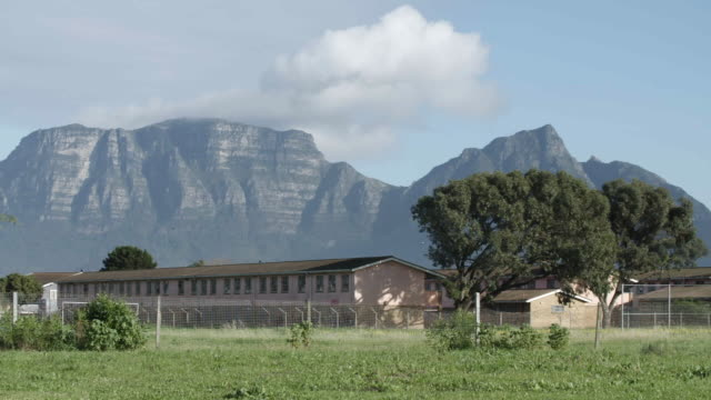 vídeos de stock, filmes e b-roll de wide pan, south african prison and table mountain in background - áfrica meridional
