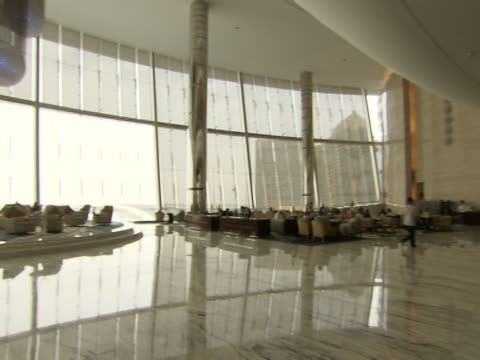 wide pan-left of the interior of the lobby of the yas viceroy hotel with guests and staff. the hotel is an icon of modern architecture in abu dhabi. - architecture stock videos & royalty-free footage