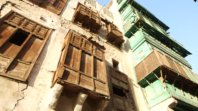 wide pan-left of wooden latticed windows on buildings in the historic centre of jeddah. - jiddah点の映像素材/bロール