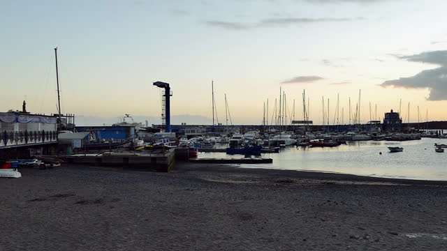 wide, panning, a marina in the golden hour, santa cruz de tenerife, spain - pier stock videos & royalty-free footage