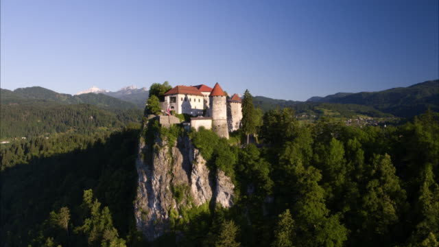 Wide panning aerial shot of castle on cliff / Bled, Slovenia