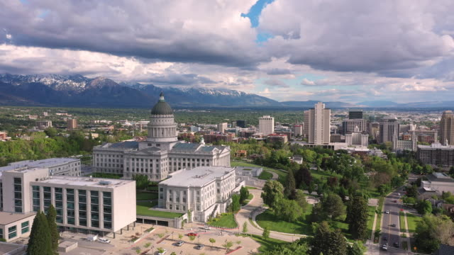 vidéos et rushes de wide panning aerial view of salt lake city and traffic driving next to the capitol - salt lake city