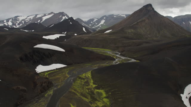 Wide panning flyover shot of snow on mountain range / Iceland