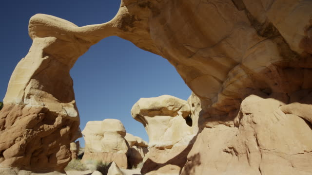 Wide panning low angle shot of arch rock formation / Escalante, Utah, United States