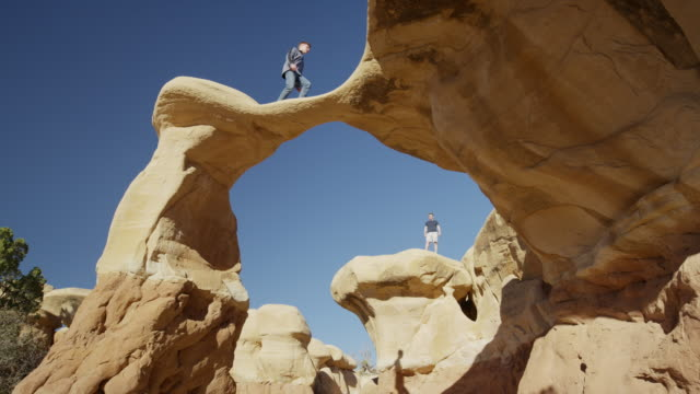 wide panning low angle shot of man walking on arch rock formation / escalante, utah, united states - escalante stock-videos und b-roll-filmmaterial