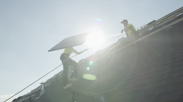 wide panning low angle shot of workers carrying solar panel on roof / mapleton, utah, united states - industriegerät stock-videos und b-roll-filmmaterial