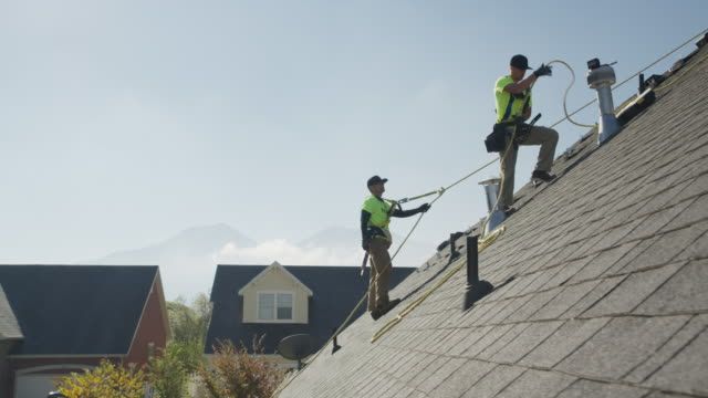 wide panning low angle shot of workers drilling on roof / mapleton, utah, united states - imbracatura di sicurezza video stock e b–roll