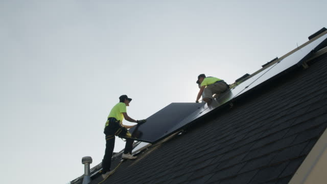 wide panning low angle shot of workers installing solar panel on roof / mapleton, utah, united states - energieindustrie stock-videos und b-roll-filmmaterial
