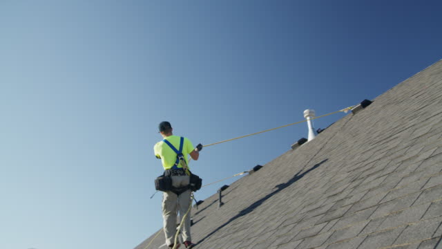 wide panning low angle shot of workers on roof checking safety lines / mapleton, utah, united states - safety harness stock videos & royalty-free footage