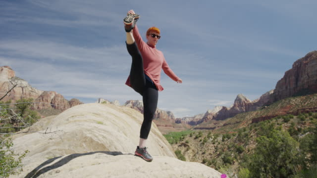 wide panning low angle view of woman balancing on boulder / zion national park, utah, united states - pedal pushers stock videos & royalty-free footage