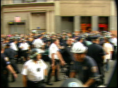 Wide panning shot across a crowd of protestors and police at the RNC 2004 antiwar protests in NYC