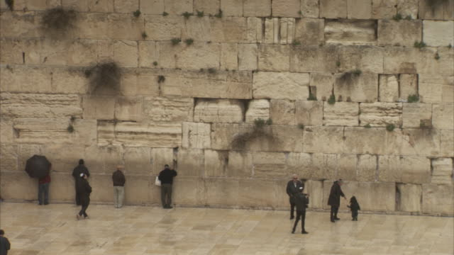 stockvideo's en b-roll-footage met wide, panning shot of a family posing for a photograph against the western wall in jerusalem. - bedevaart
