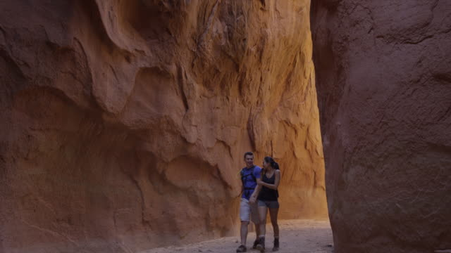 wide panning shot of affectionate couple hiking in narrow canyon / escalante, utah, united states - escalante stock-videos und b-roll-filmmaterial