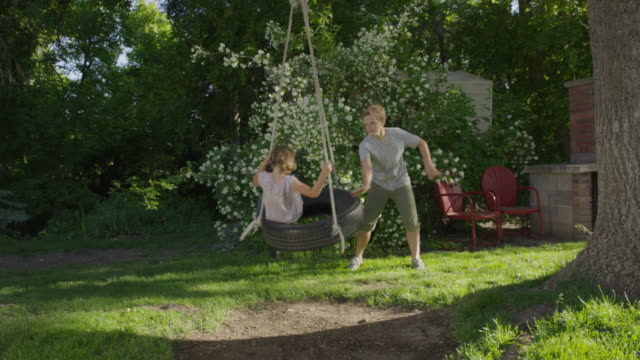 wide panning shot of boy pushing girl on tire swing / springville, utah, united states - springville utah stock-videos und b-roll-filmmaterial