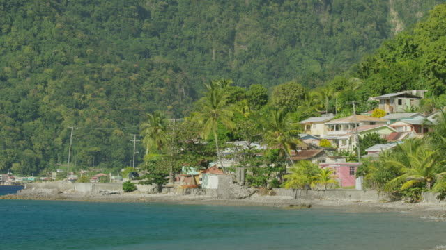 Wide panning shot of car driving past waterfront houses / Scotts Head, Dominica
