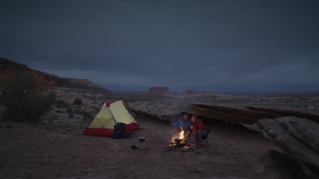 Wide panning shot of couple at campfire in desert / Moab, Utah, United States