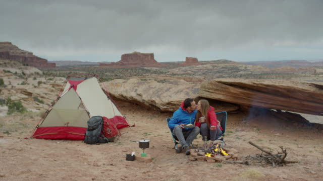 wide panning shot of couple at campfire in desert / moab, utah, united states - moab utah stock videos and b-roll footage