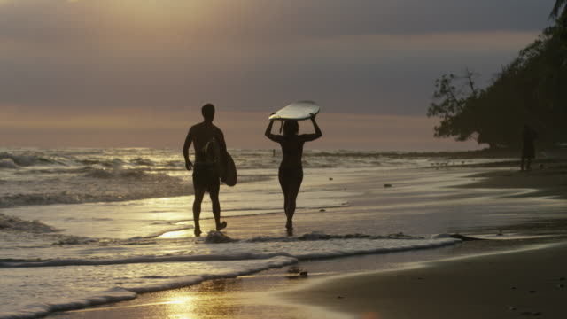 Wide panning shot of couple carrying surfboards on beach at sunset / Esterillos, Puntarenas, Costa Rica