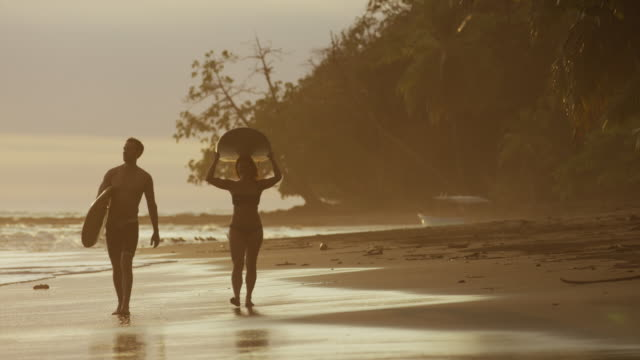 wide panning shot of couple carrying surfboards on beach / esterillos, puntarenas, costa rica - water sport stock videos & royalty-free footage