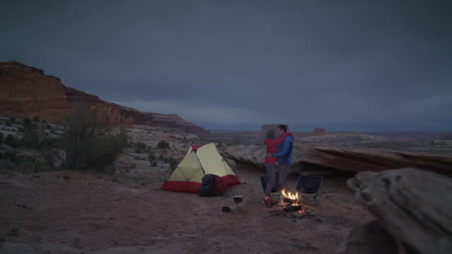 wide panning shot of couple dancing at campfire in desert / moab, utah, united states - moab utah stock-videos und b-roll-filmmaterial