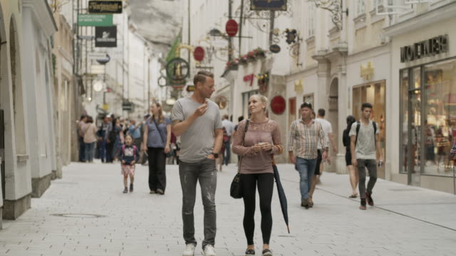 Wide panning shot of couple eating ice cream in busy street / Salzburg, Austria