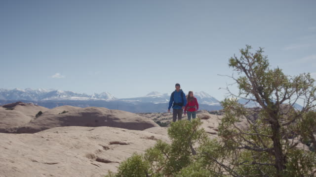 wide panning shot of couple hiking in desert / moab, utah, united states - ユタ州モアブ点の映像素材/bロール