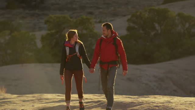 wide panning shot of couple hiking in desert / moab, utah, united states - moab utah stock videos and b-roll footage